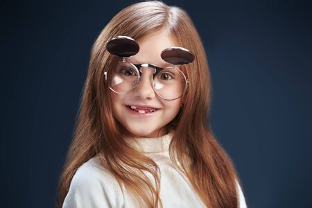 Portrait of a funny little girl in glasses on a dark background. Fashion trends for kids. Stock Photo