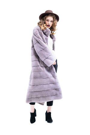 A full length portrait of thoughtful beautiful girl wearing a lilac fur coat. Beauty, winter fashion.