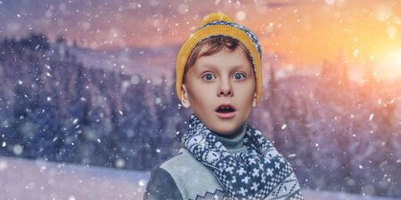 Funny excited boy child in knitted hat and a scarf stands under the snowfall against the background of a winter landscape and he is surprised. Copy space. Banque d'images