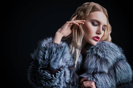 Un ritratto di una bella donna che indossa una pelliccia e occhiali da sole. Bellezza, moda invernale, stile. Archivio Fotografico