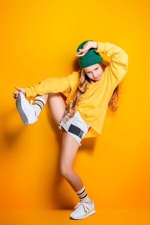 Eine Aufnahme in voller Länge eines hellen emotionalen Mädchens. Mode für aktive Kinder.