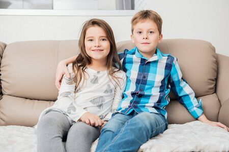 Cute boy and girl are  sitting on the couch.  Fashion home shot. Childhood. Kid's fashion. Stockfoto - 134739551