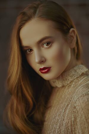 Portrait of a beautiful young girl with natural make-up and in a light beige dress on a brick wall background. Beauty and cosmetics concept. Lifestyle.