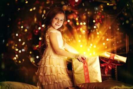 Cute little girl sits with a gift box by a beautiful Christmas tree. Christmas and New Year concept. The atmosphere of magic, lights and sparkle is around.
