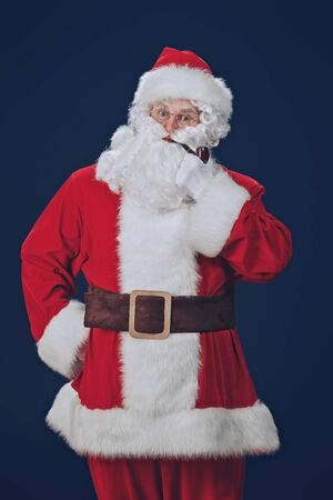 Merry Christmas and Happy New Year! Funny Santa posing with a pipe in his mouth on dark blue background.