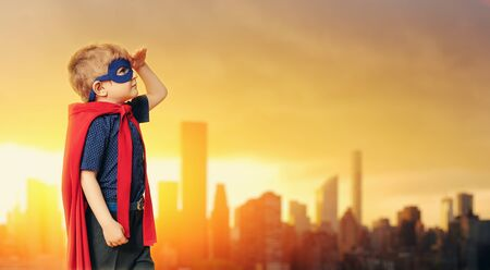 A portrait of a funny young boy posing in the costume of superhero. Kids development and education concept.