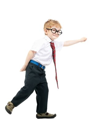 A full length portrait of a happy young schoolboy posing in the studio over the white background. Kids fashion for school, education.