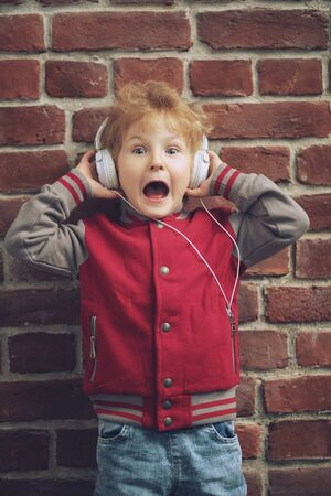 A portrait of a young schoolboy posing in the studio over the brick wall and listening to music in the headphones. Kids casual fashion, education. Stock Photo