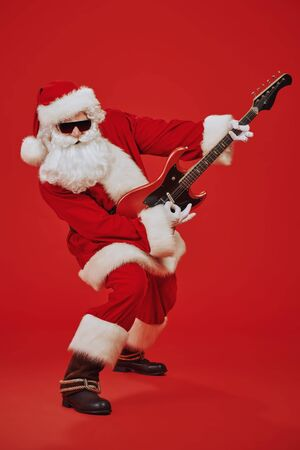 Cool Santa Claus rock musician with electric guitar and in sunglasses on a festive red background. Christmas and New Year party. Standard-Bild - 135211104