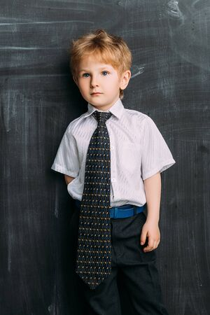 A portrait of a tired young schoolboy near the blackboard. Kids fashion for school, elementary school, education.