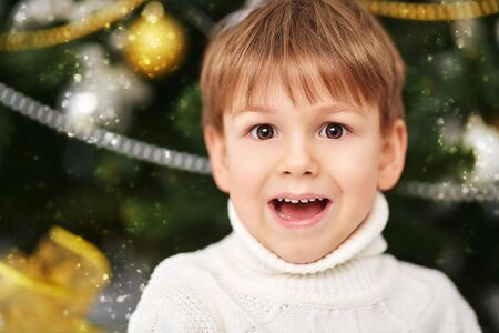 Funny little boy in winter clothes sits next to the Christmas tree next to gifts. The atmosphere of a magical holidays. Christmas and New Year concept. Reklamní fotografie