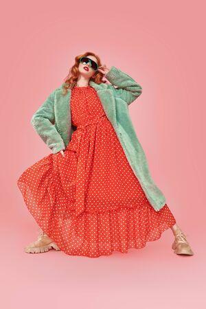 Ganzaufnahme einer modischen jungen Frau, die in einem langen roten Kleid und einem Pelzmantel posiert. Mode erschossen. Standard-Bild