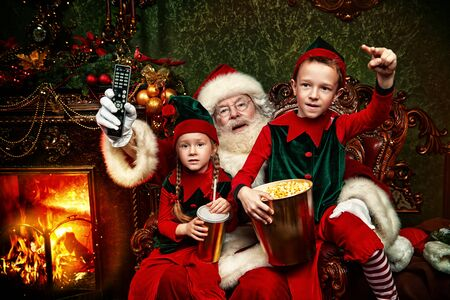 Cheerful Santa Claus and elves watching a movie with soda and popcorn in a house beautifully decorated for Christmas. Entertainment and cinema concept.