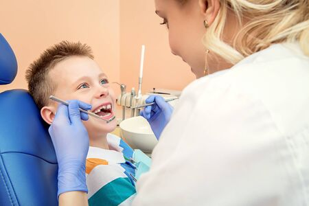 Gesundheitswesen, Medizin. Kinderzahnheilkunde. Zahnarztdoktor behandelt die Zähne eines Kinderjungen in einer Zahnarztpraxis. Standard-Bild