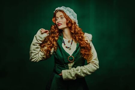 Portrait of a beautiful young woman with long red hair wearing medieval clothes on a dark green background. Historical reconstruction of the early Middle Ages. 免版税图像