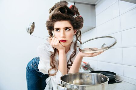 Pretty young woman with hair curlers on the head is bored standing in the kitchen with a ladle. Beauty, fashion concept. Pin-up style.