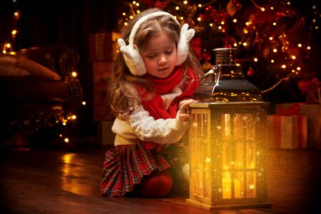 Wesołych Świąt i Szczęśliwego Nowego Roku! Uśmiechnięta mała dziewczynka siedzi z latarnią w domu obok pięknej choinki.