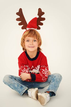 Merry Christmas and Happy New Year! Cute little boy with Christmas deer horns on his head and in a festive red knitted sweater smiles at the camera. Studio portrait over white background. Reklamní fotografie