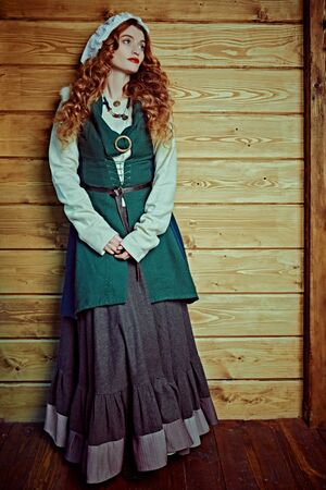 Full length portrait of a beautiful young woman with long red hair wearing medieval clothes on a wooden background. Historical reconstruction of the Middle Ages.