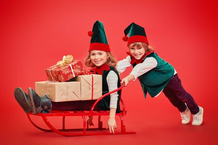 Cute little boy and girl elves Santa Claus helpers are pushing the sled with gifts. Studio portrait over festive red background. Christmas and New Year concept.