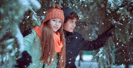 Two happy young people walking in a beautiful winter park. Winter holidays.
