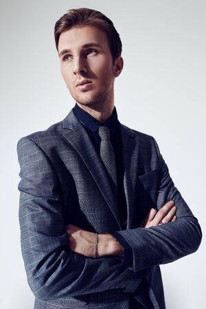 Een portret van een knappe jonge zakenman in een formeel pak in de studio. Herenmode.