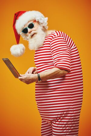 Modern Santa on vacation working on laptop. Bright yellow background. Copy space. Christmas and New Year concept.