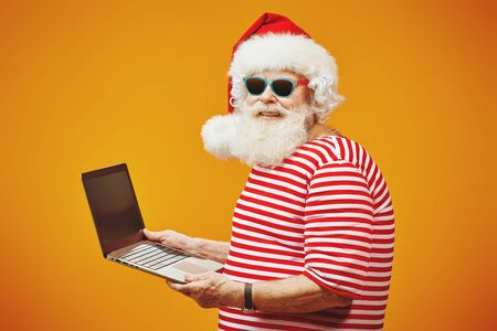 Modern Santa Claus on vacation working on laptop. Bright yellow background. Copy space. Christmas and New Year concept. Stock Photo