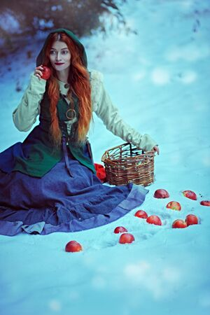 Winter fairy tale. Beautiful young woman with magnificent red hair sits on a snow in a winter forest with red apples scattered around. Historical reconstruction of the Middle Ages.