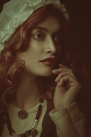 Close up portrait of a beautiful young woman with long red hair wearing medieval clothes on a dark green background. Historical reconstruction of the Middle Ages.