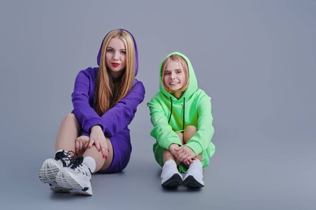 Two sisters in bright sweatshirts pose in the studio. Youth style and fashion. Foto de archivo