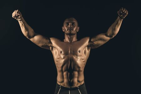 Portrait of a handsome athletic man with perfect muscular body over black background. Bodybuilding concept. Healthy lifestyle. Reklamní fotografie