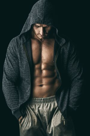 Handsome athletic man in hoodie posing over black background. Sports and bodybuilding concept. Healthy lifestyle. Reklamní fotografie