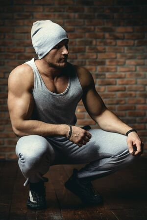 Muscular athletic man stands by a brick wall. Sport lifestyle.  Bodybuilding.