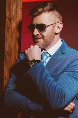 A portrait of a brutal handsome man in sunglasses. Mens beauty, fashion. Optics for men.