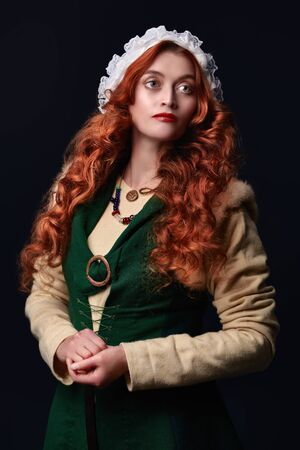 Portrait of a beautiful young woman with long red hair wearing medieval clothes on a dark green background. Historical reconstruction of the Middle Ages.