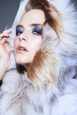 A close up portrait of a beautiful woman wearing a fur coat with hood. Beauty, winter fashion, style.