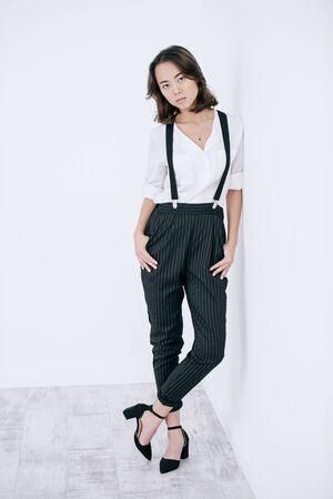 Junge asiatische Frau gekleidet in weißem Hemd und klassischer Hose, die im Studio aufwirft. Business-Stil in der Kleidung. Mode erschossen.