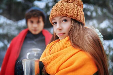 A young girl and her boyfriend spend time together happily in the winter forest. Winter season, winter activities.