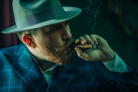 A portrait of a thoughtful man with a cigar posing in the vintage interior. Mens beauty, fashion, style. Zdjęcie Seryjne