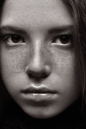 Close-up portrait of a beautiful young girl with freckles looking at camera. Studio portrait. Banco de Imagens