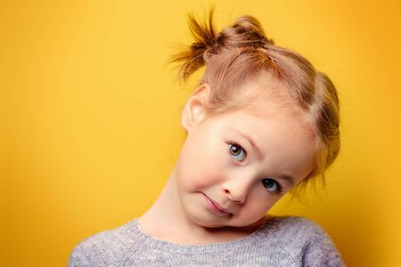 Close-up portrait of a funny emotional girl over yellow background. Childhood concept.