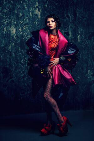Female beauty, fashion. Full length portrait of a female model posing in stylish clothes. Studio shot over grunge background.