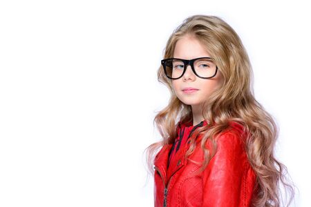 Cute ten year old girl posing in studio in red leather jacket. Isolated over white. Beauty, fashion.