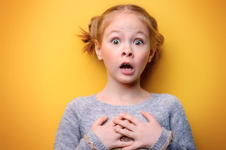 Close-up portrait of a funny emotional girl making faces at camera. Studio shot over yellow background. Childhood concept. Standard-Bild