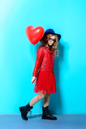 Full length portrait of a pretty ten-year-old girl holding heart shaped balloon over blue background. Valentine's Day. Children's fashion.
