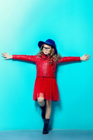 Full length portrait of a pretty happy pre-teen girl over blue background. First love. Valentine's Day.