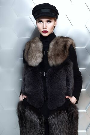 A portrait of a beautiful girl wearing a hat and fur coat. Beauty, winter fashion.