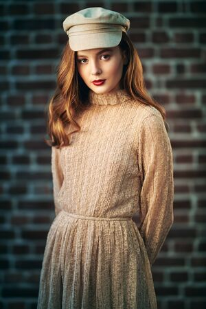 Portrait of a pretty modern girl with natural make-up and in a light beige dress and a cap standing in a room with loft interior. Brick wall background. Beauty, fashion concept. Reklamní fotografie