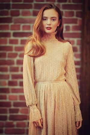 Pretty young girl with natural make-up and in a light beige dress stands in a room with loft interior and smiles slightly. Brick wall background. Beauty, Fashion concept.
